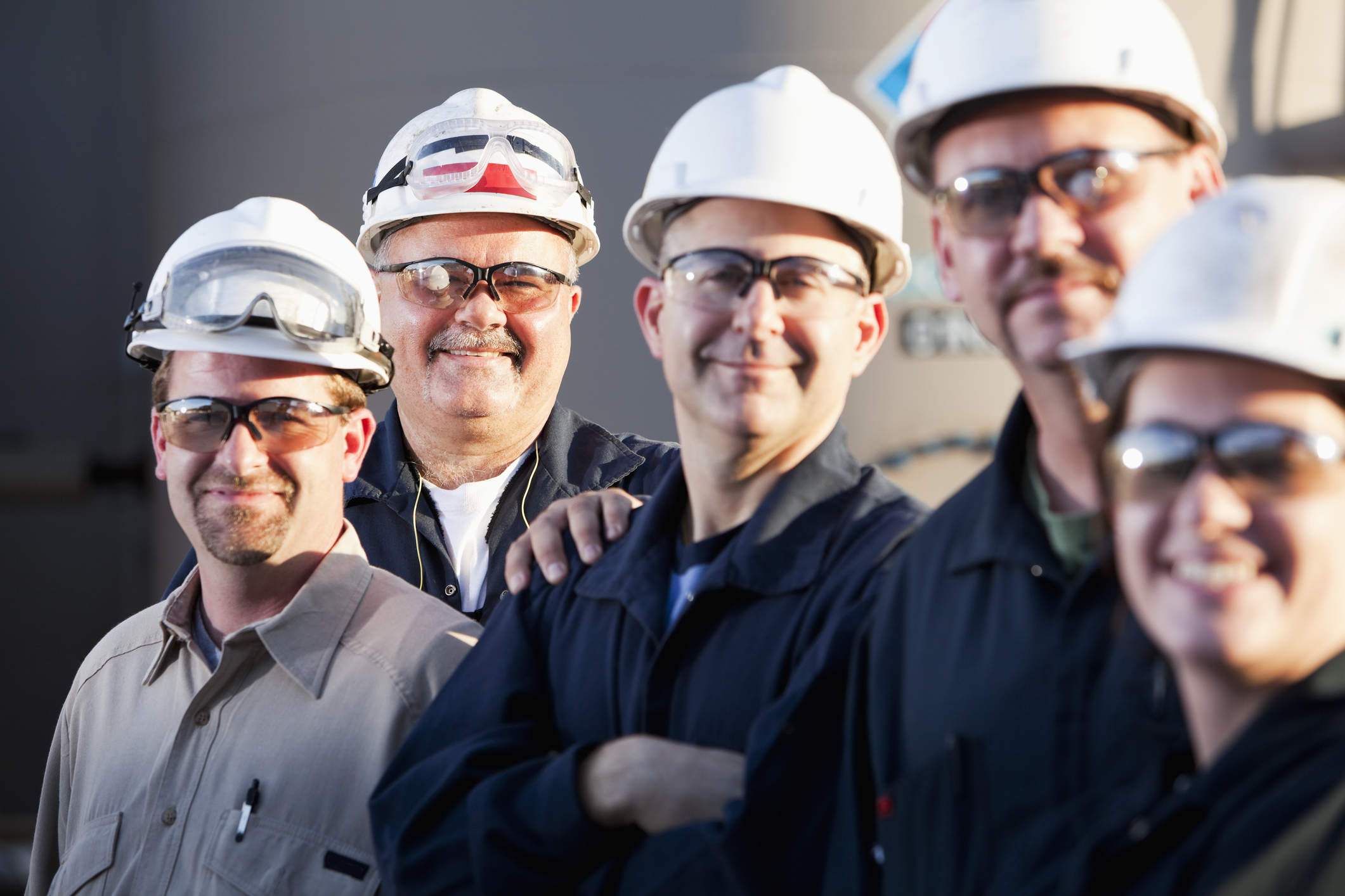 Close up of a group of five industrial workers standing in front of a storage tank. They are wearing white hardhats, safety glasses and dark blue or tan uniforms. There are four men and one woman standing and smiling at the camera. The man in the middle has his arms folded. The focus is on the man in the back, 2nd from the left.