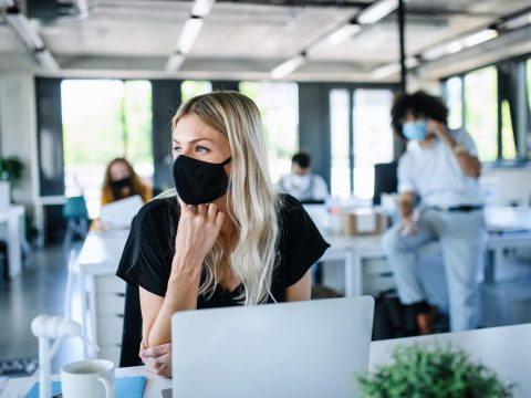 young woman in face mask back at work in an office